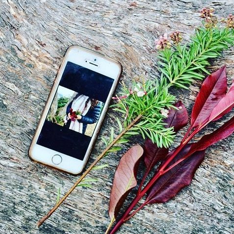 flatlay image of iphone and foraged flora for living flow yoga content